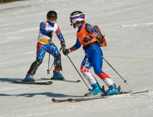 100% blind athlete Lindsay Ball being guided through the icy slalom course by Dianne Barris