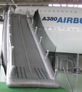 The escape slide from the 3 story (8 metre) high upper deck door sill. Rocket powered venturi pump inflates slides within 6 seconds (2/3 is fresh air). Inflates within 6 seconds. Withstands 25 kts (46 kmph) winds.