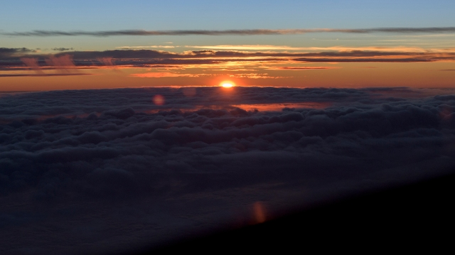 Sunrise between the Pacific marine layer cloud and upper level cloud. Taken from 38,000 feet,24 October 2015. 300 nm west of Los Angeles. (Photo: RDC)